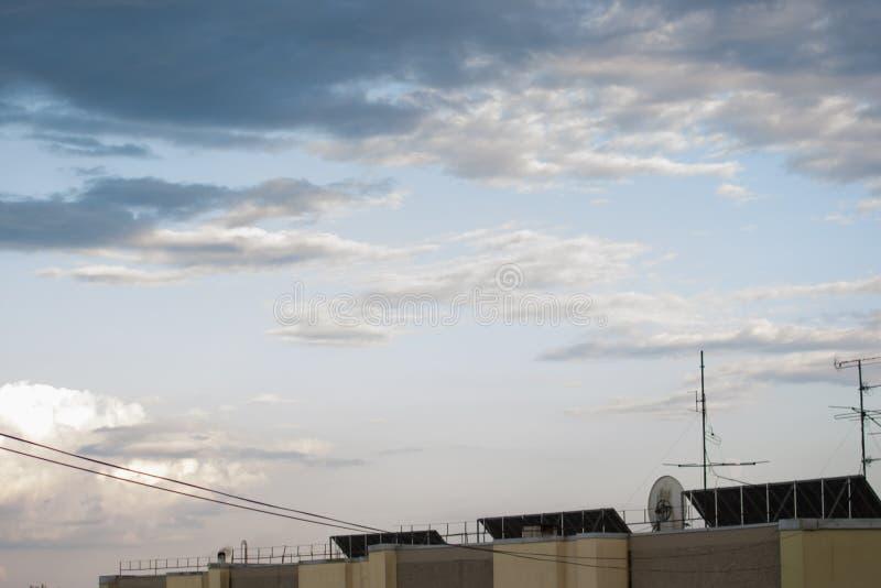 Telhado da construção com os três painéis solares e a antena satélite foto de stock