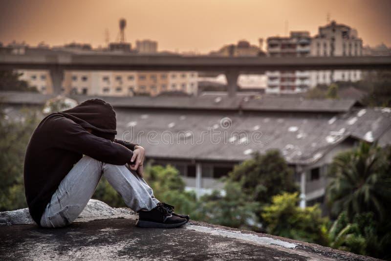 Telhado de assento do homem asiático novo da construção com stre da depressão fotos de stock