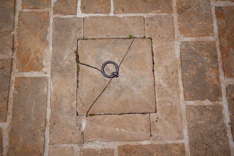 Telhado de pedra, anel oxidado no meio dos pavers velhos imagens de stock