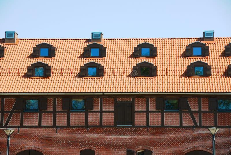 Telhado de telha com janelas de uma casa velha do tijolo fotos de stock royalty free