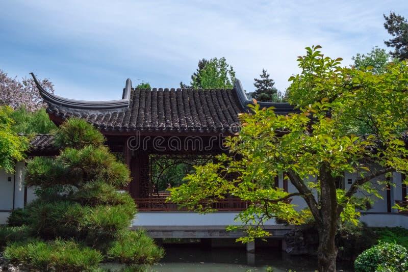 Telhado de uma construção chinesa tradicional, cercado pela vegetação em um espaço livre, Sunny Day em um jardim botânico chinês imagens de stock