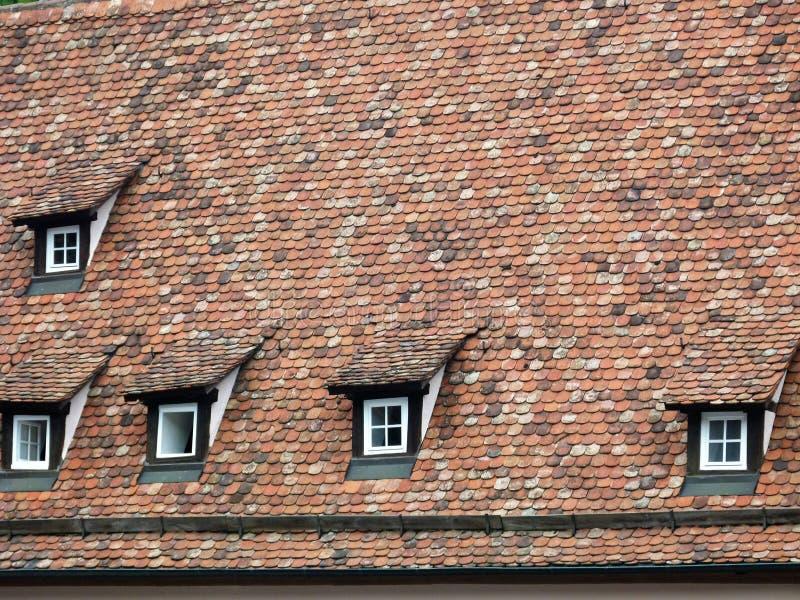 Telhado de uma construção da Idade Média adiantada com tijolos antigos e algumas janelas de trapeira foto de stock