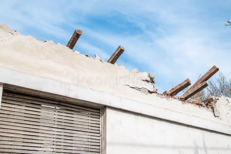 Telhado desmoronado danificado e quebrado da casa abandonada após o fogo da bomba da granada, com fundo da janela quebrada e do c fotos de stock royalty free