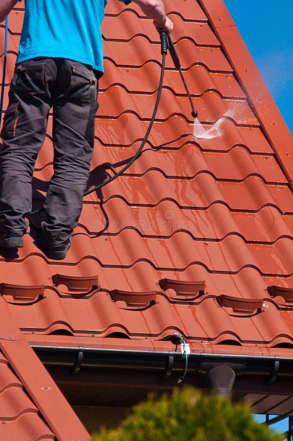 Telhado do metal da limpeza do trabalhador com água de alta pressão foto de stock royalty free