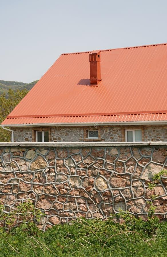 Telhado e cerca vermelhos da pedra foto de stock