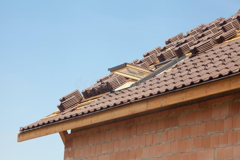 Telhado novo com claraboia aberta, telha vermelha natural contra o céu azul fotografia de stock royalty free