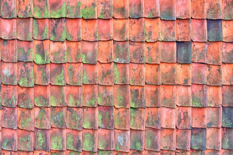Telhado velho coberto com o redroof coberto com os telhados vermelhos das telhas, os velhos e arruinada Textura de um telhado com fotos de stock