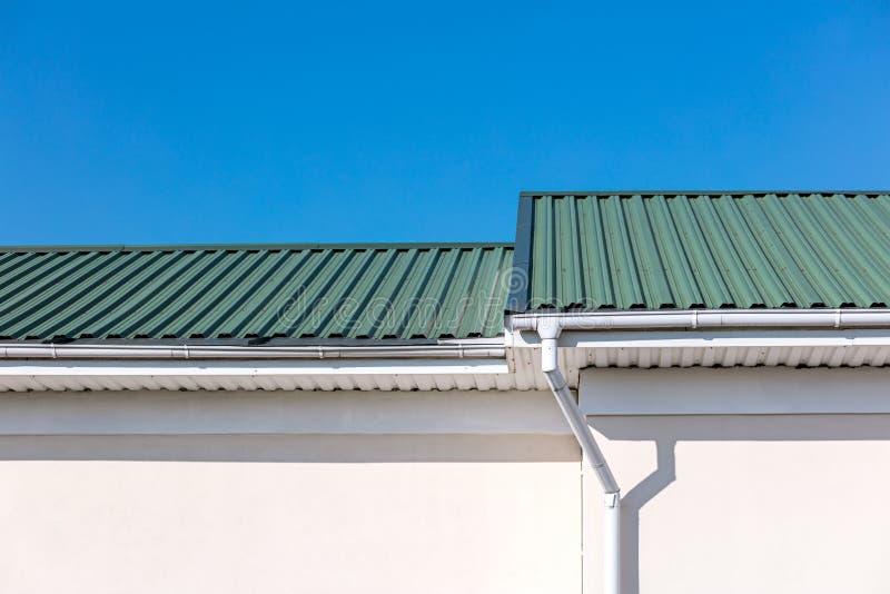 Telhado verde das tubulações e do downspout recentemente construídos da calha do metal branco da casa no fundo do céu azul fotografia de stock royalty free