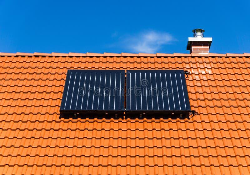 Telhado telhado vermelho com a planta térmica e a chaminé solares fotografia de stock royalty free