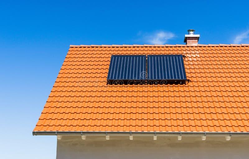 Telhado telhado vermelho com a planta térmica e a chaminé solares fotos de stock royalty free