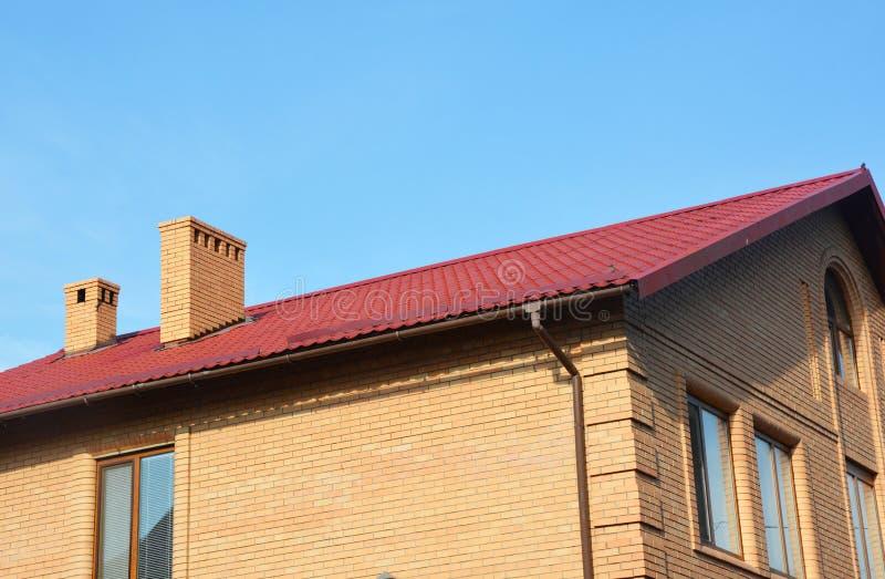 Telhado vermelho do metal da casa do tijolo com sistema de encanamento olastic da calha da chuva imagens de stock