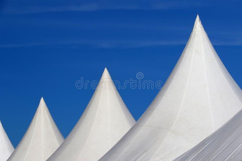 Telhados brancos das barracas alinhadas sobre o céu azul fotos de stock royalty free