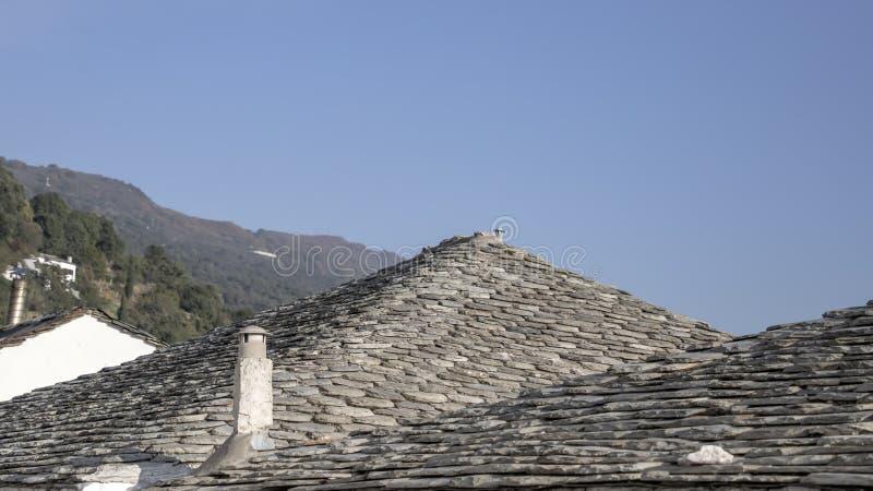 Telhados telhados com chaminés contra um céu azul e uns montes verdes imagens de stock