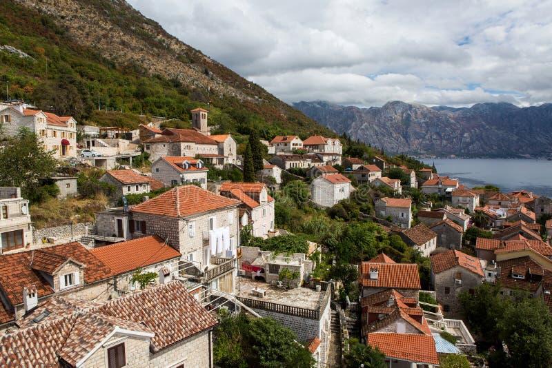 Telhados de casas velhas em Perast e em baía com as montanhas em Montenegro imagens de stock royalty free