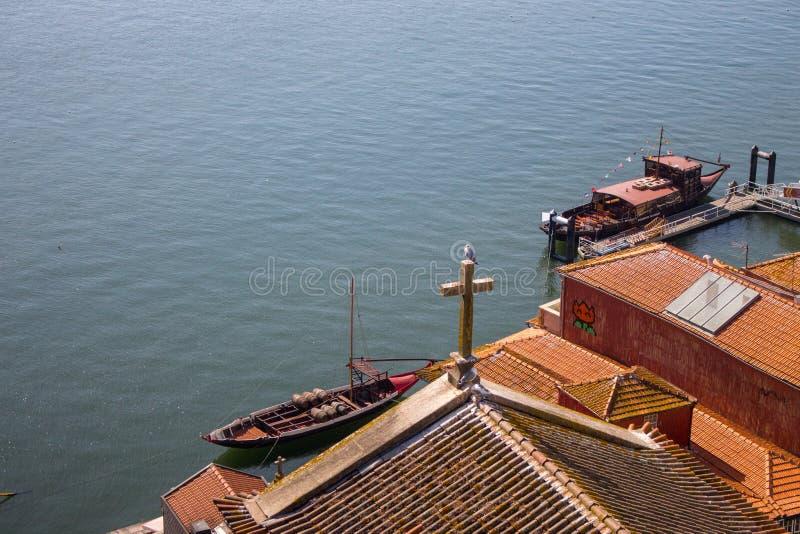 Telhados vermelhos com cruz na opinião superior do fundo de Douro do rio Terraplenagem com telhado da igreja e cruz de madeira em foto de stock
