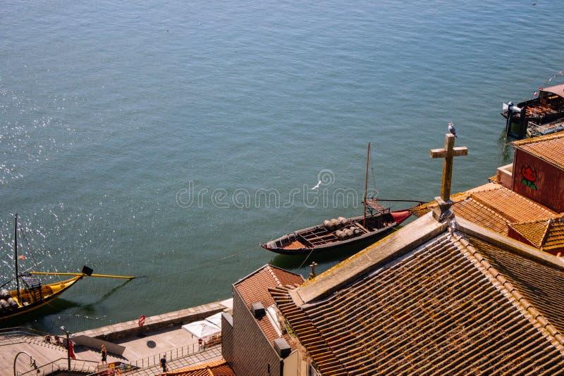 Telhados vermelhos com cruz na opinião superior do fundo de Douro do rio Terraplenagem com telhado da igreja e cruz de madeira em imagens de stock