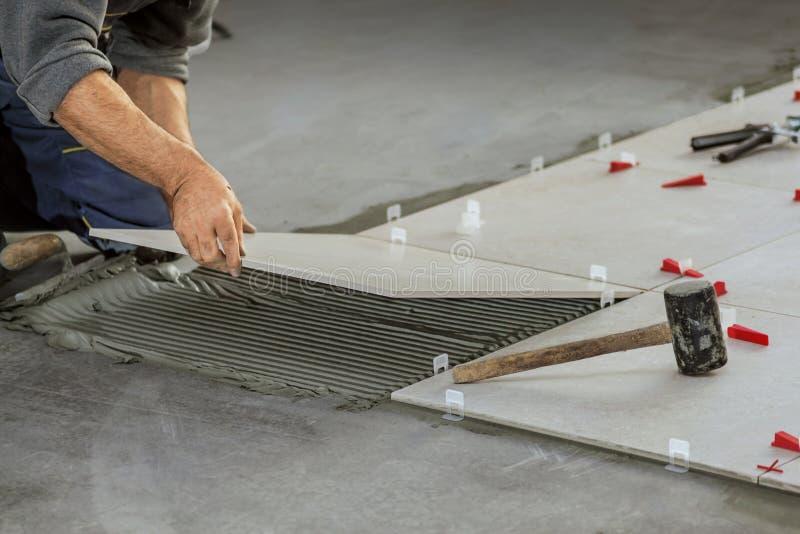 Telhas cerâmicas Tiler que coloca a telha cerâmica da parede em posição sobre fotos de stock