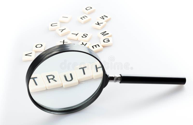Telhas da lupa e do alfabeto arranjadas em uma verdade da palavra imagens de stock