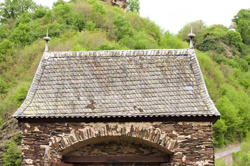 Telhas de telhado pretas de uma construção gótico com um arco do tijolo imagens de stock
