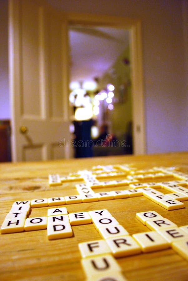 Telhas do jogo de palavras do Scrabble em uma sala de visitas confortável foto de stock