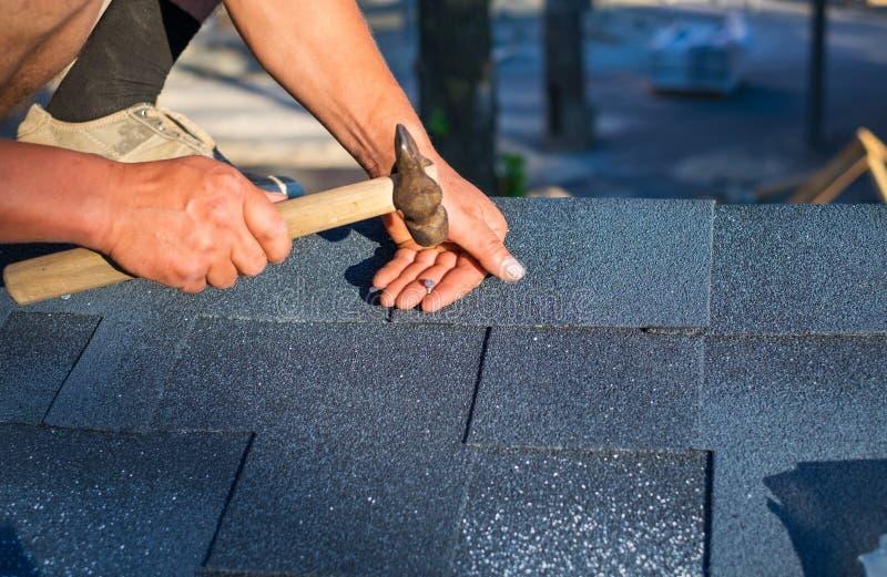 Telhas do telhado do betume do canto do reparo do trabalhador com martelo e pregos imagem de stock