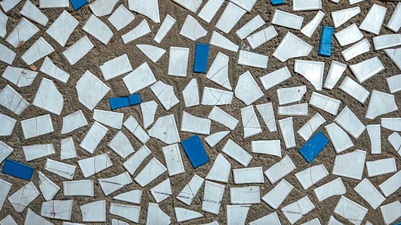 Telhas velhas no concreto, mosaico, cerâmica quebrada na construção Fundo de uma casa na cidade fotos de stock royalty free