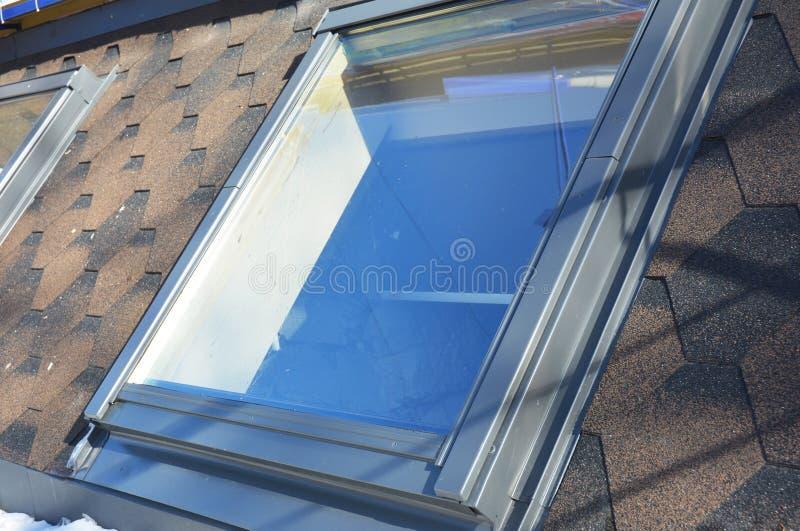 Telhe a instalação das janelas e das claraboias com a neve no inverno imagem de stock