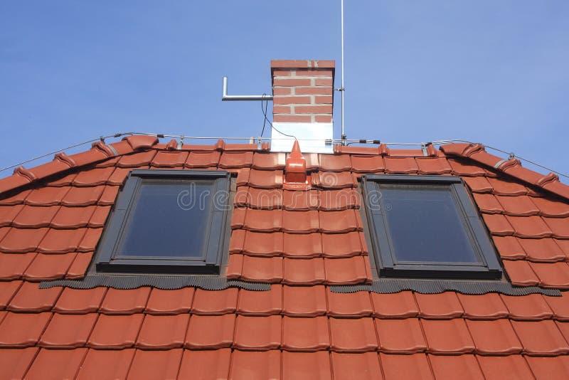 Telhe janelas, telhas da argila, chaminé e relâmpago fotografia de stock royalty free