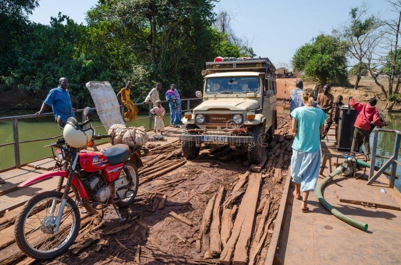 Telimele,几内亚- 2013年12月21日:摩托车, 4x4车,简单的木筏的, Fouta Djallon人横渡的河 库存照片