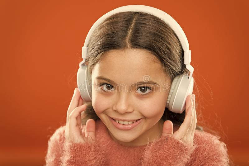 Tell me what you listen to, and I will tell you who you are. Girl cute little child wear headphones listen music. Kid. Listen music orange background stock images