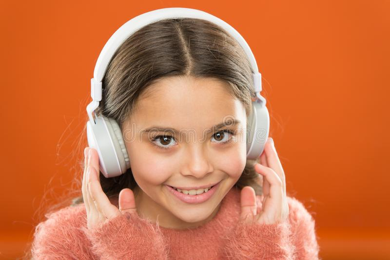 Tell me what you listen to, and I will tell you who you are. Girl cute little child wear headphones listen music. Kid. Listen music orange background royalty free stock image