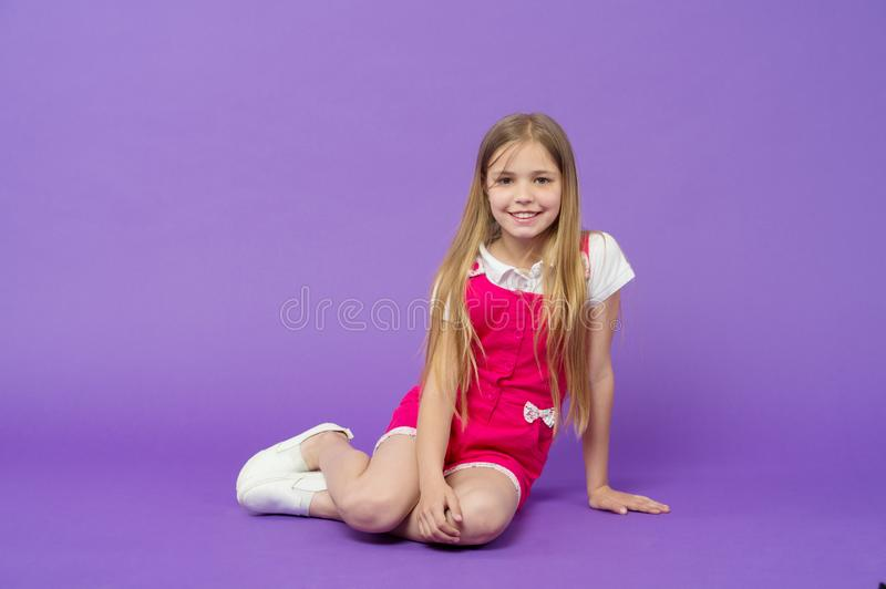 Tell me your story. Girl happy face sit on floor ready listen story violet background. Kid girl with long hair cute. Outfit relax wait interesting story. Child stock photo