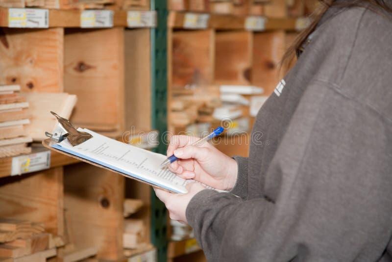 Tellende inventarisproducten bij een lumberyard stock afbeelding