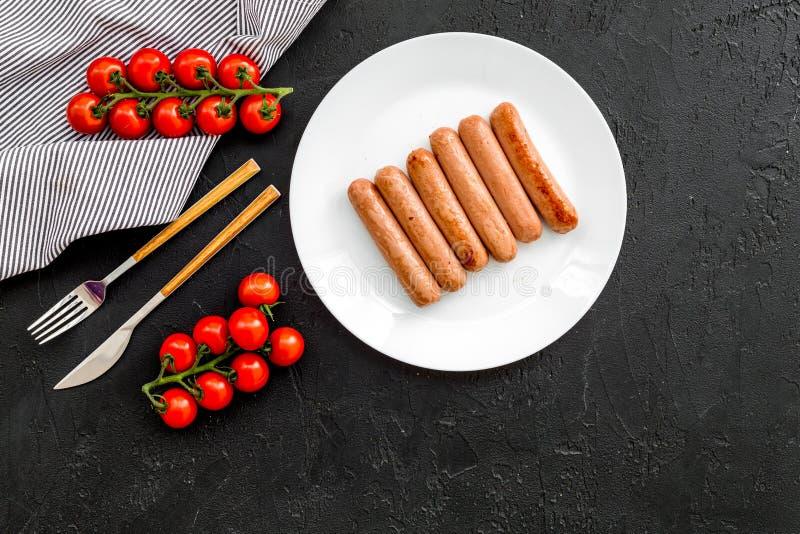 Teller auf dem Grill schnell und einfach zu kochen Gebratene Würste nahe Kirschtomaten auf schwarzem Draufsicht-Kopienraum des Hi lizenzfreies stockbild