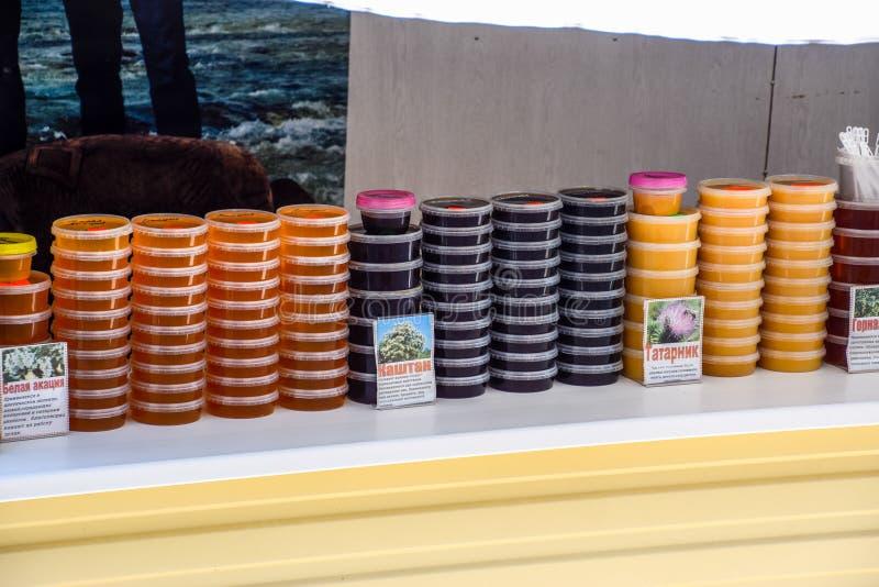 Teller met honing Verschillende types van honing in blikken Verkoop van honing royalty-vrije stock foto