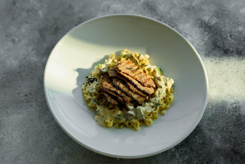 Teller mit Fleischstücken, -teigwaren, -GRÜNS und -soße von Fettleber stockbild