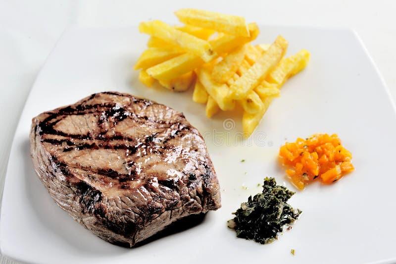 Teller mit gegrilltem Fleisch Fleisch, Pommes-Frites begleitet von chimichurri Soße stockbild