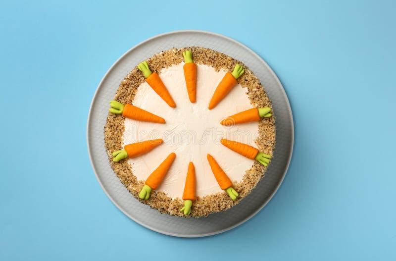 Teller mit geschmackvollem Karottenkuchen auf blauem Hintergrund stockfotografie