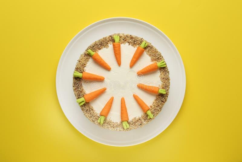 Teller mit geschmackvollem Karottenkuchen auf gelbem Hintergrund stockfotografie