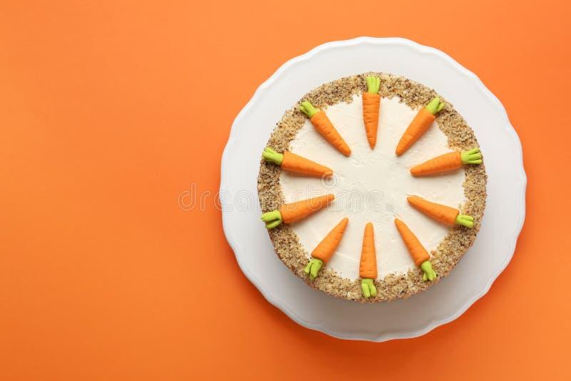 Teller mit geschmackvollem Karottenkuchen auf orange Hintergrund, Draufsicht lizenzfreie stockfotografie