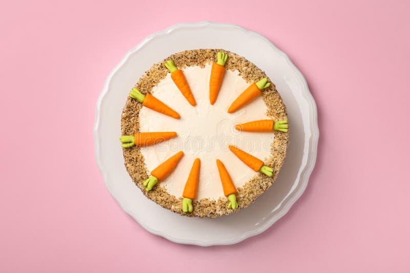 Teller mit geschmackvollem Karottenkuchen auf rosa Hintergrund stockfotografie