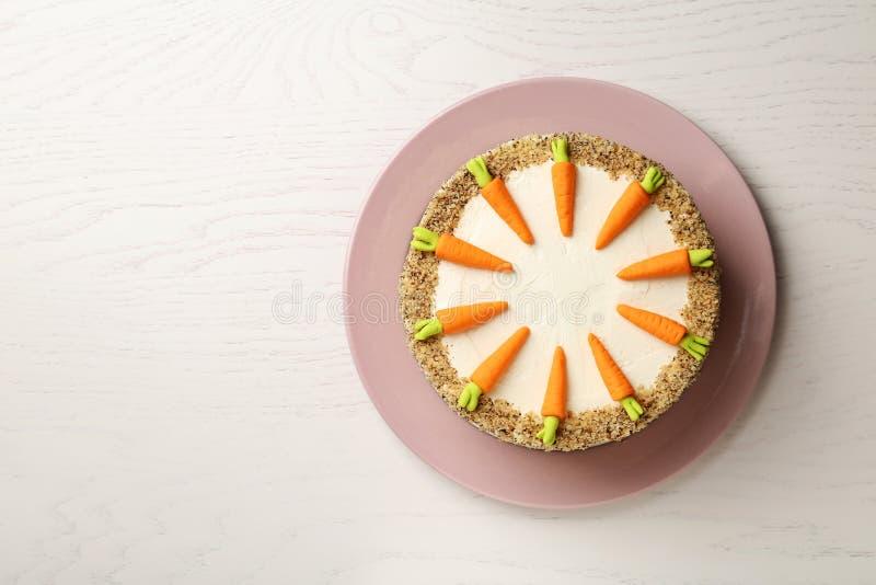 Teller mit geschmackvollem Karottenkuchen auf weißem Holztisch, Draufsicht stockbilder