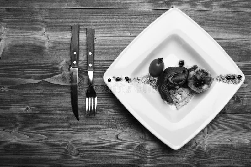 Teller mit moderner Darstellung auf quadratischer Platte Französische Mahlzeit stockfotos