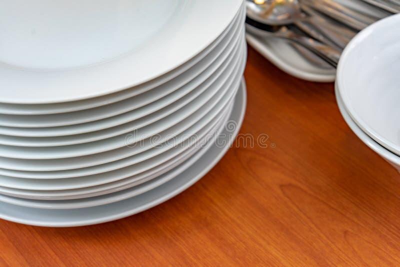 Teller, Platten, Schüsseln, Löffel, Gabel sind, vorbereitend vereinbarend und auf hölzerne Tabelle für das Buffetmittagessen oder stockfotos