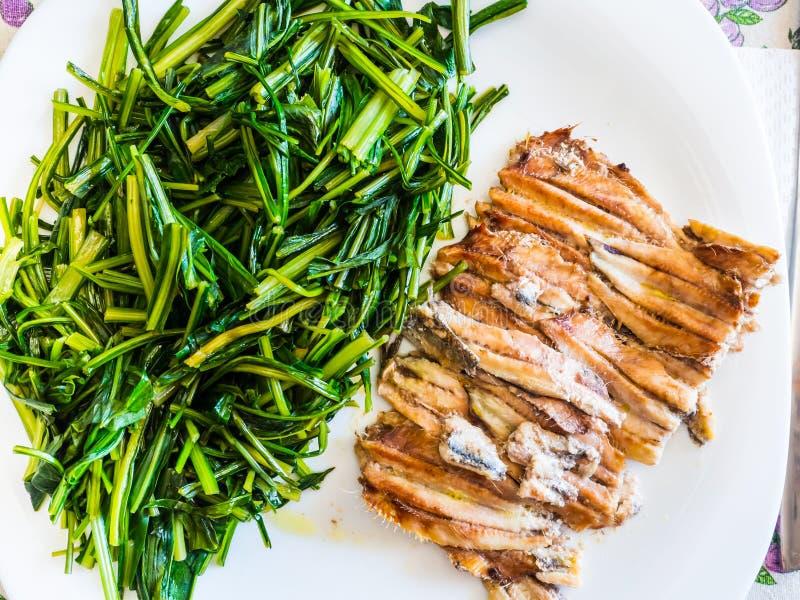 Teller von gebackenen Sardellen mit Zichorie lizenzfreie stockbilder