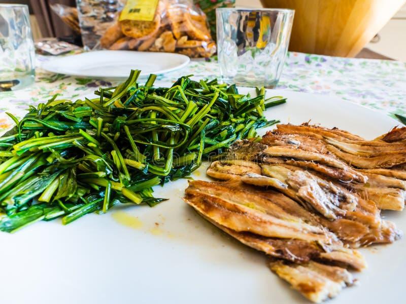 Teller von gebackenen Sardellen mit Zichorie stockbild