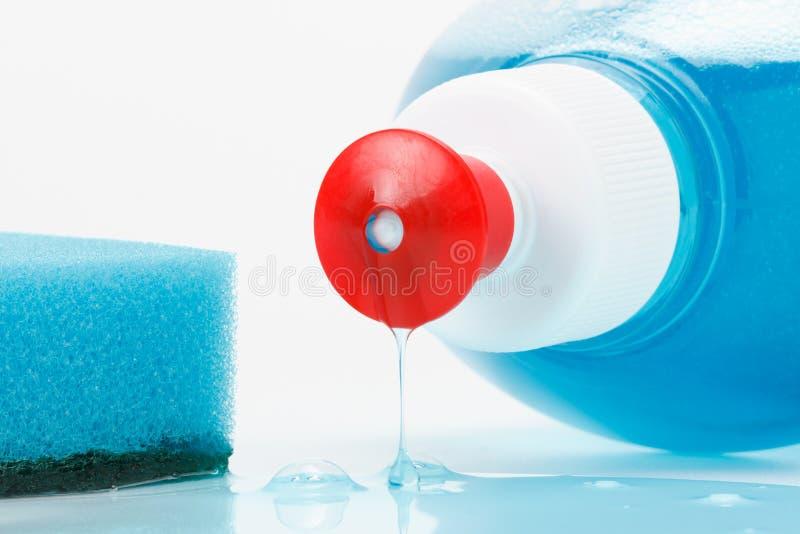Tellerreinigungflüssigkeit fließt aus der Flasche heraus lizenzfreies stockbild