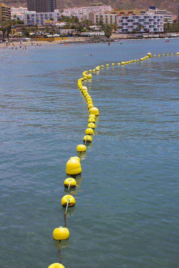 Tellersboeien om zwemmers te verhinderen ingaand die een gebied naast de pijler door boten en kleine ambacht in de baai bij Los C stock fotografie