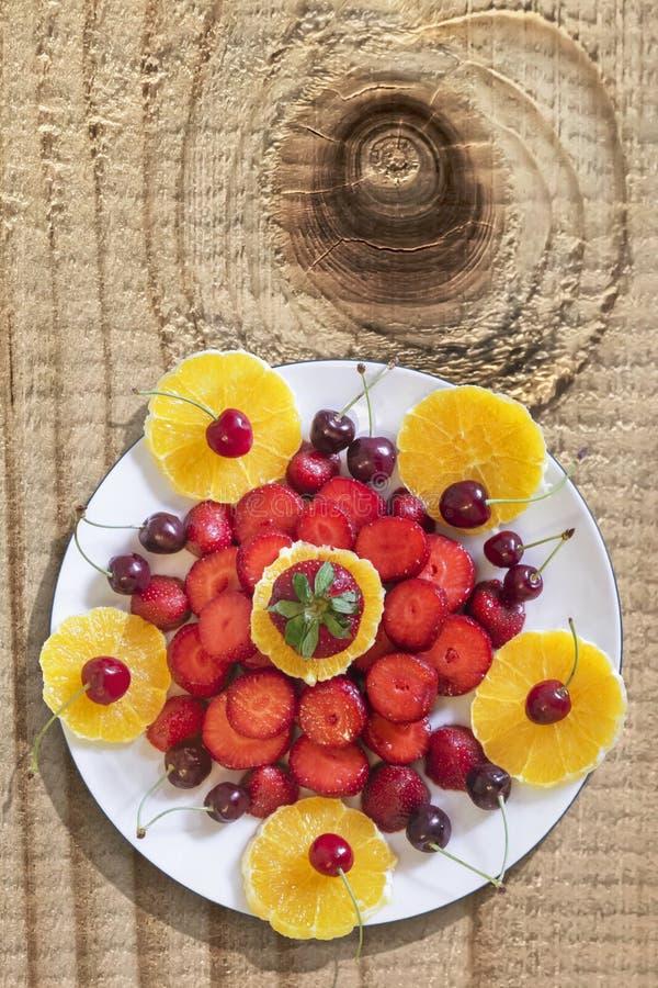 Tellervoll Frühlings-Früchte auf alter hölzerner geknoteter Tischplatte stockfotos