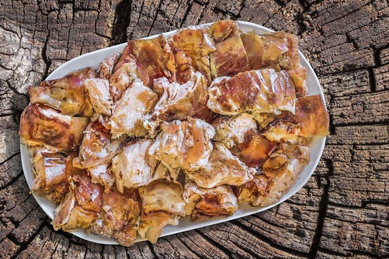 Tellervoll Spucken gebratene Schweinefleisch-Scheiben eingestellt auf alter Stumpf verwitterte Sprungs-Oberfläche stockfotos